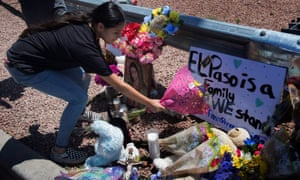 A woman places flowers beside a makeshift memorial outside the Walmart.