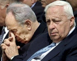 Peres looks down and Sharon looks sombre; both in dark suits