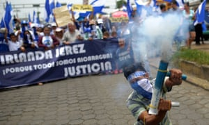 An anti-government demonstrator fires a home-made mortar as he takes part in a march demanding the resignation of Nicaraguan President Daniel Ortega and his wife