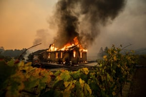 Vines surround a burning building as the Kincade fire burns through the Jimtown community of unincorporated Sonoma county.