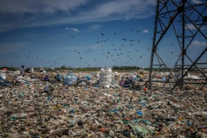 Families work in a rubbish dump encroaching on a wetland in an industrial district in Chennai