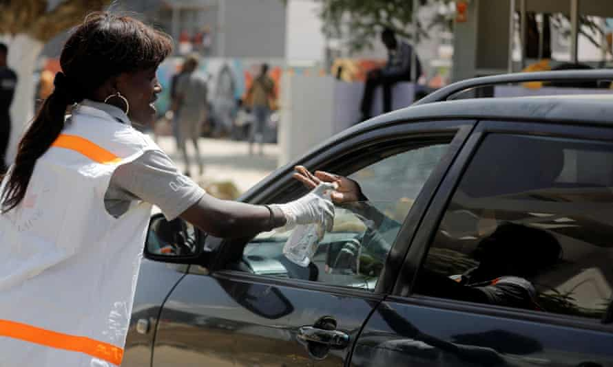A Red Cross worker pours a sanitising gel into a driver's hand in Dakar, Senegal.