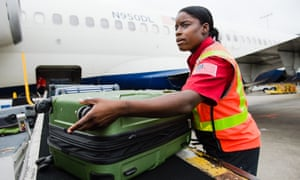 Charlessa Brightwell helps load luggage onto an airplane.