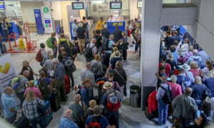 People line up in front of the Thomas Cook desk at Heraklion airport on Crete