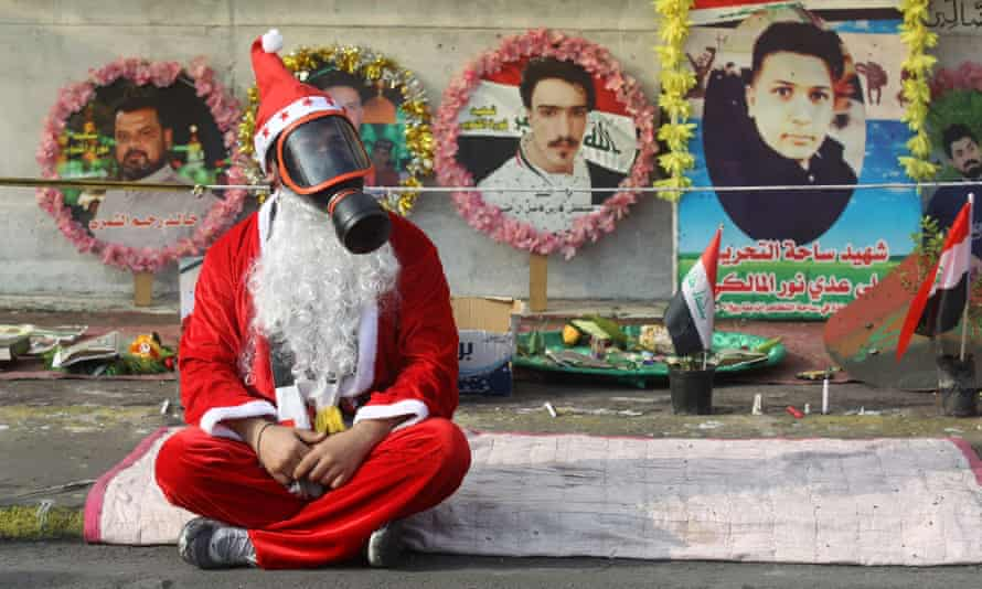 An Iraqi demonstrator in Tahrir Square with a gas mask on and wearing a Santa suit