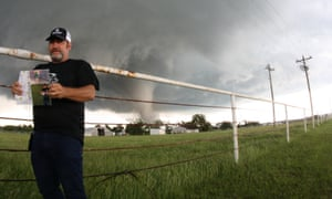 Stormchaser and tour guide Bill Rhode stands in front of a field; behind him a tornado starts to build and the sky is grey.