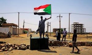 A Sudanese protester holds a national flag as he stands on a barricade along a street in Khartoum.