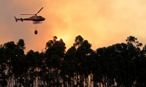 A helicopter combats a forest fire in Monchique