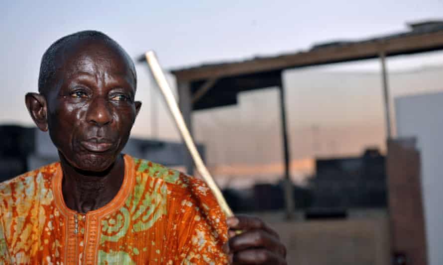 Doudou N'diaye Rose holding his sabar drumstick.