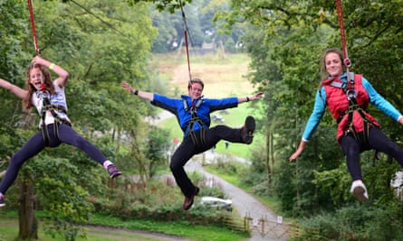 The Manchester Treetop Trek will be similar to this one in Windermere. Image shows guide and two children in harnesses enjoying a tree trek.