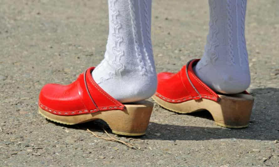 A girl wears white stockings and red clogs.