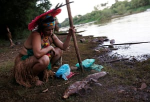 An indigenous woman looks at dead fish near the Paraopeba river in the Cerrado.