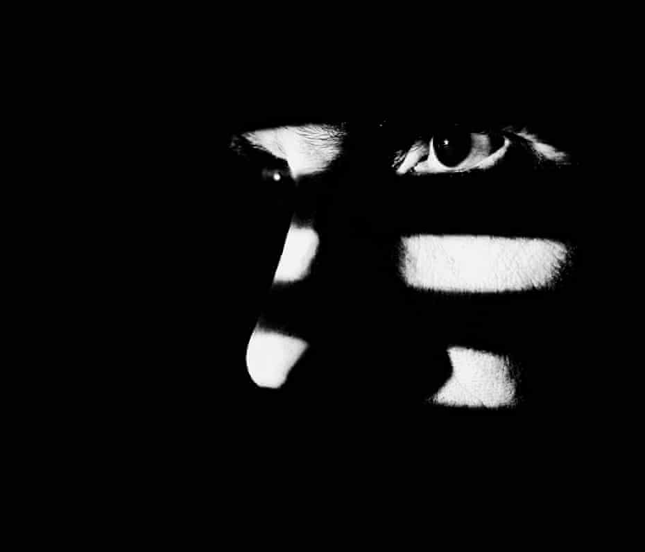 Close up of a male face illuminated through a window blind.