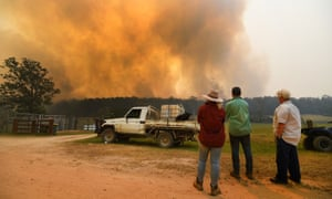 Locals watch smoke from a large bushfire outside Nana Glen, near Coffs Harbour
