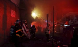 Baltimore firefighters rush ladders into position as blazes rage through the night.