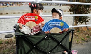 Children wearing face masks hold fans as they wait along the route of the Tokyo 2020 Olympic torch relay, during the coronavirus pandemic