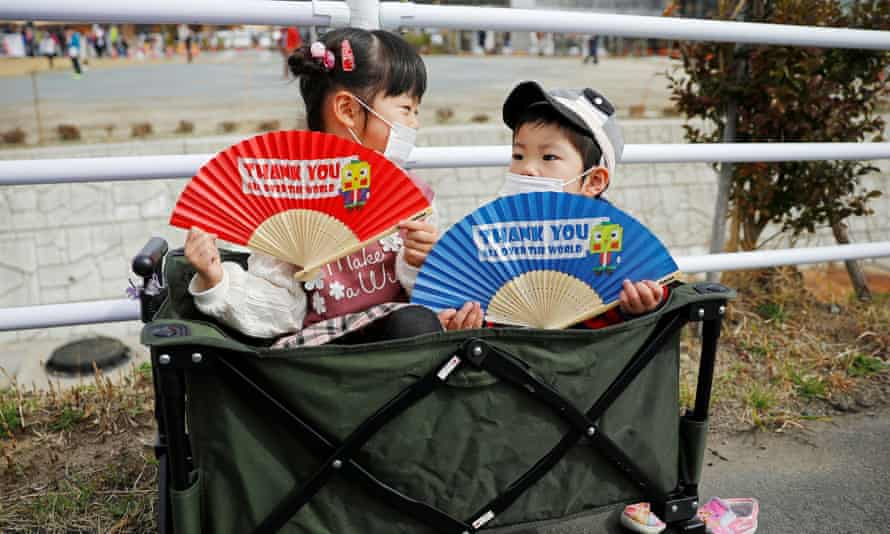 Children wearing face masks hold fans as they wait along the route of the Tokyo 2020 Olympic torch relay, during the coronavirus pandemic.