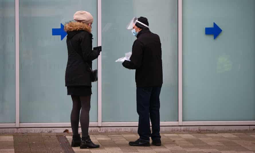 A worker wearing PPE speaks to a woman outside a coronavirus test centre in north Kensington.