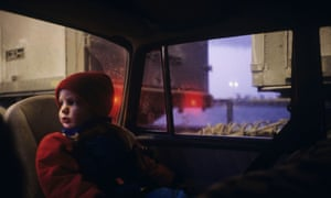 A child sitting in a backseat and looking through the window