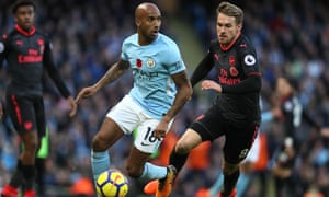 Manchester City's Fabian Delph gets past Aaron Ramsey during the Premier League match against Arsenal on Sunday.