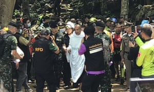 Rescuers help Phra Manas, centre, walk out of the cave on Wednesday.