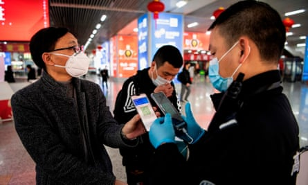 A person wearing a face mask displays a green QR code on his phone to show his health status to security at a train station in Wenzhou, China