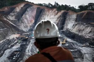 A worker on a break looks over an open-pit coal mine in Makroman, East Kalimantan, Indonesian Borneo