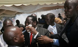 Opposition leader Raila Odinga (centre) is protected by bodyguards during a funeral service for victims of the violence in Nairobi, 2008.