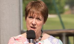 Caroline Spelman speaks into a microphone in the sun