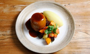 A round plate with a suet pudding with dark gravy over it, a neat pile of vegetables and an oval of mash