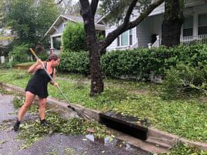 Accrina Grandin sweeps debris off the street in front of her home.