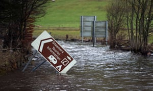 Flood water surrounds a damaged road sign