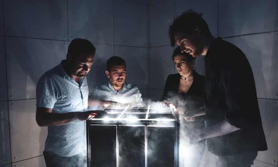 A team of four, in a dark room, play the escape room game Escapologic, Nottingham and Leicester.