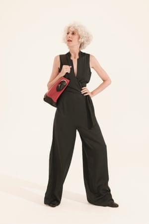 black sleeveless jumpsuit, red and black shoulder bag, black boots
