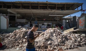 A man walks past a destroyed store after a 6.4 earthquake hit on Tuesday in Guánica, Puerto Rico.