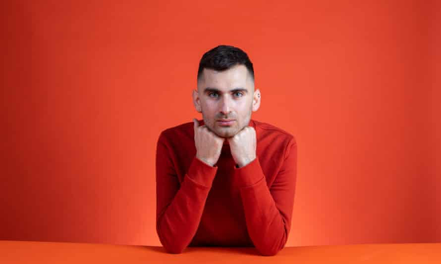 Michael Segalov in a red jumper leaning his chin on his fists. On an orange background