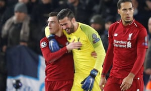 Alisson celebrates among Andy Robertson and Virgil van Dijk after the win over Napoli.