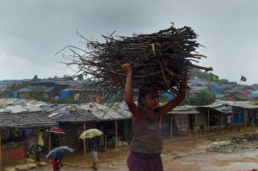 A child carries wood as rain falls at Jamtoli, another of the refugee camps in Cox's Bazar