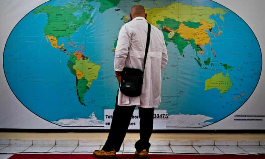 Cuban doctor Ralfis Carbort looks at a map of the world before leaving to help with the devastation caused by Hurricane Idai.