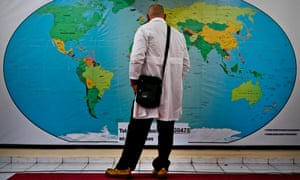 A Cuban doctor contemplates a map of the world