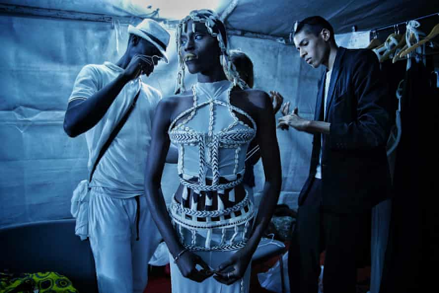 Designer Oumar Dicko (right) of Mali and Belgium laces up a model in one of his creations backstage, July 2017