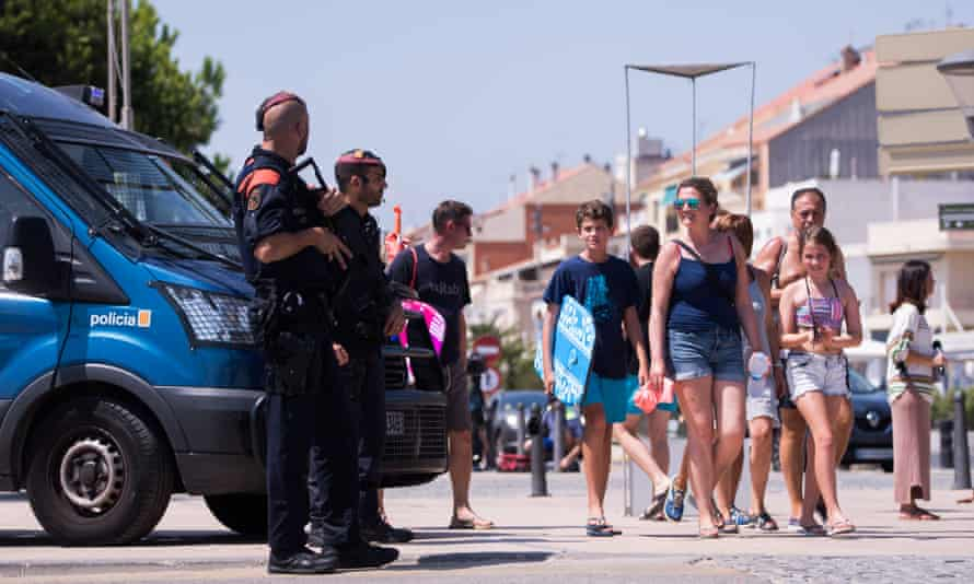 Beachgoers walk past police officers in Cambrils, Spain