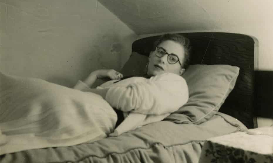 A young Monica Jones lies on a bed.