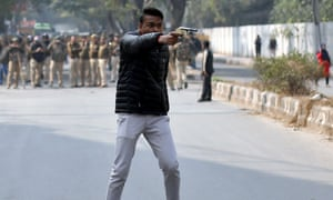 An unidentified man brandishes a gun during a protest against a new citizenship law outside the Jamia Millia Islamia university in New Delhi.