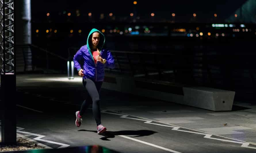 A woman jogging in the city at night