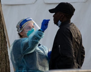 A medical technician administers a test to a resident at a Covid-19 testing site in East Boston, Massachusetts on 3 December.