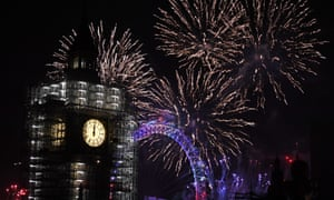 Fireworks explode over Big Ben and the London Eye at midnight.