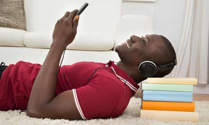 A man on the floor listens to headphones
