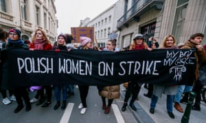 People hold banners while they take part in a rally during the International Women's Day in Brussels, Belgium.