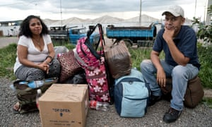 Venessa Márquez and Jesús Andrade sit with their possessions just after crossing the Venezuelan border into Brazil.